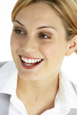 Head-and-shoulders photo of dark blonde woman smiling, for free teeth whitening from Plano femal dentist Dr. Miranda Lacy.