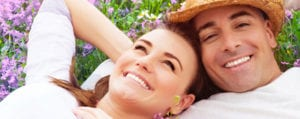 Head and shoulders photo of a man and woman lying in a field of flowers, for information on sedation dentistry from Plano TX dentist Dr. Miranda Lacy.