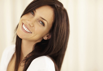 Closeup, head-and-shoulders photo of a brunette woman smiling with her head slightly tilted back; for information on Plano affordable dentistry and cosmetic dentistry options.
