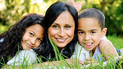 Outdoors close-up photo of a mother and children smiling and lying on grass. The dark-haired mother is in the middle, her daughter is pictured left, and her son is on the right; for information on sedation dentistry for children.