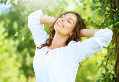 Head-to-waist photo of a brunette woman outdoors and stretching backward with her eyes closed; for information on relaxing with sedation dentistry from Plano TX female dentist Dr. Miranda Lacy.