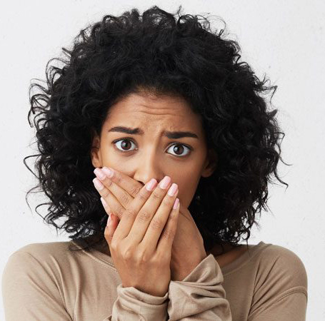 Head-and-shoulders photo of an African American woman holding her hands over her mouth; for information about bad breath and teeth whitening from Plano, TX dentist Dr. Miranda Lacy.