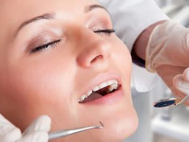 Woman's face with her eyes closed while she receives dental work