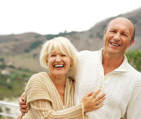 Photo of senior couple smiling outdoors for dentures from Plano dentist Miranda Lacy.