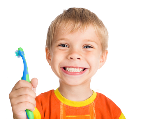 Photo of a blonde boy smiling and holding a toothbrush for Plano TX pediatric dentistry from Dr. Miranda Lacy.