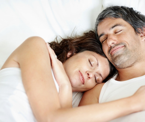 Middled aged couple sleeping with smiles on their faces for Plano snoring treatment from Miranda Lacy DDS.