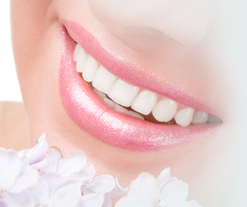 Soft touch photo of a closeup smile and white flowers for technology in the office of Plano dentist Dr. Miranda Lacy.